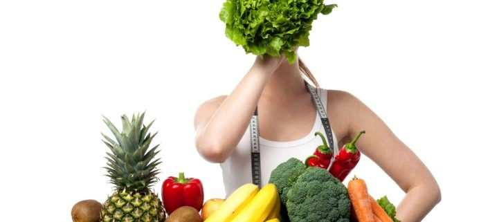 Frau mit Salt vor dem Gesicht und viel Gemüse und Obst vor sich.